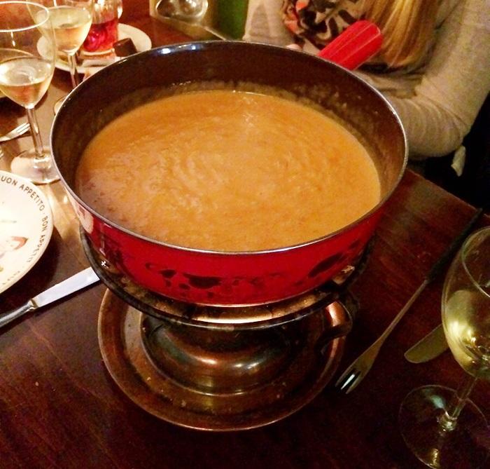 La fondue à la tomate se mange généralement avec des petites pommes de terre sur lesquelles on verse le fromage onctueux avec une louche